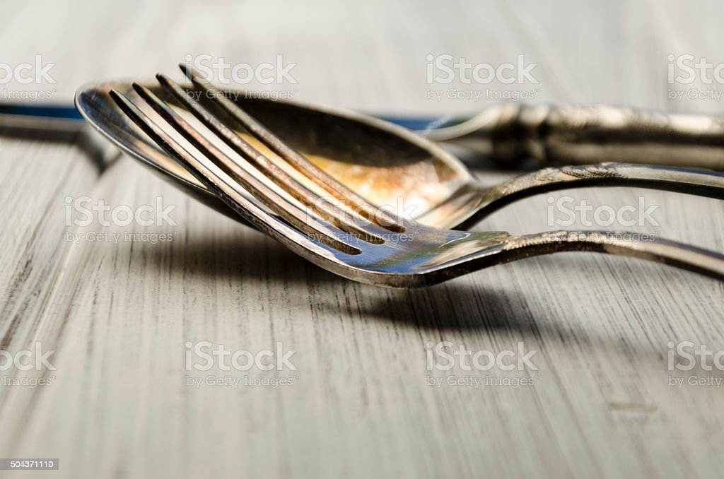 old cutlery on white wooden table stock photo