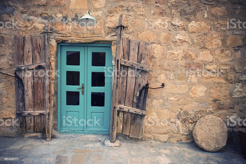 Old cyan door and natural stone wall royalty-free stock photo