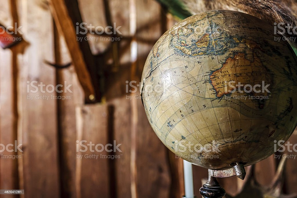 Old damaged globe against wooden wall. stock photo