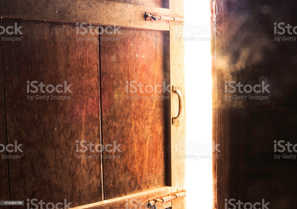 Old dark room with shining closed door. stock photo