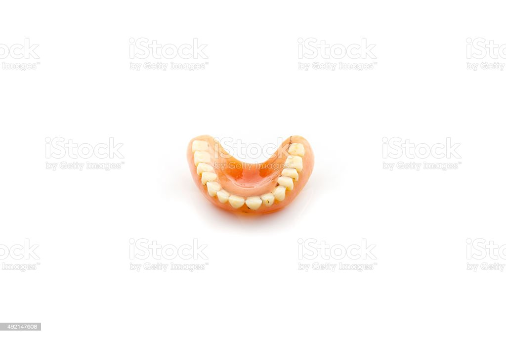 Old dentures isolated on white background. stock photo