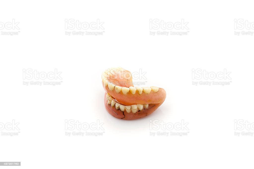 Old dentures , Through repair ,isolated on white background. stock photo