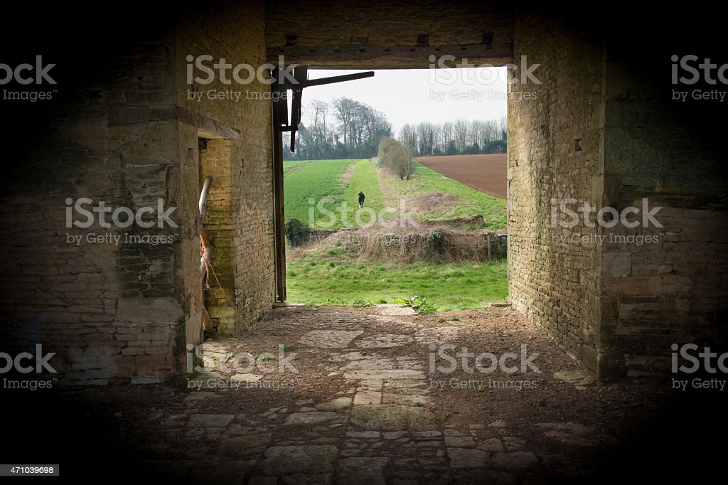 Old derelict farm building with view out onto arable land stock photo