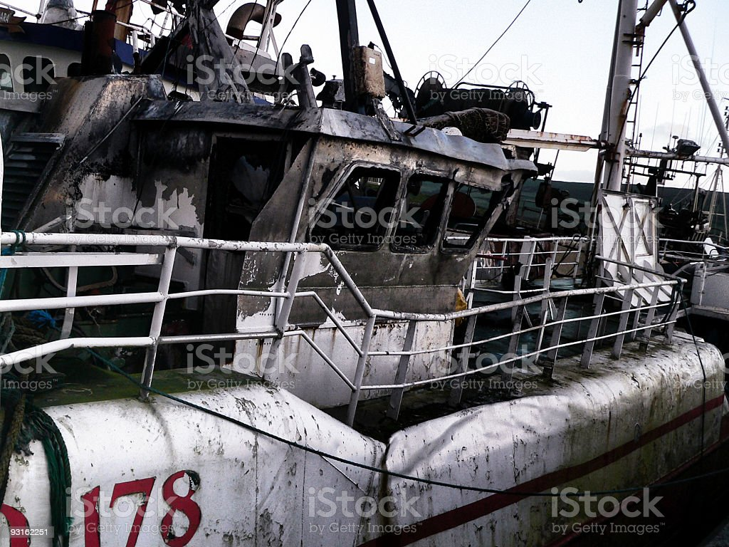 Old derelict trawler boat in harbor burnt out after fire stock photo