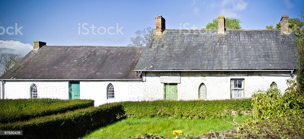 Old Deserted whitewashed Irish country cottages with green doors stock photo