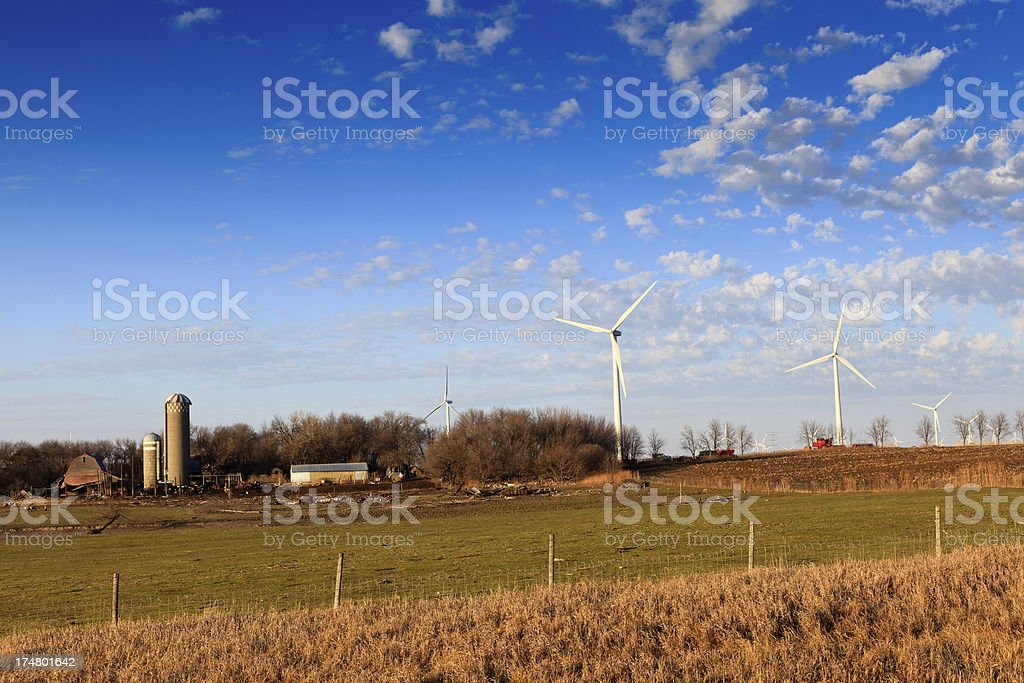 Old dilapitated farm next to new wind turbines. royalty-free stock photo