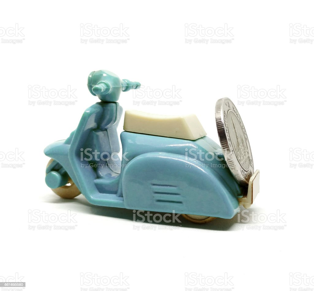 Old dirty blue scooter toy carrying coin isolated on white background. stock photo
