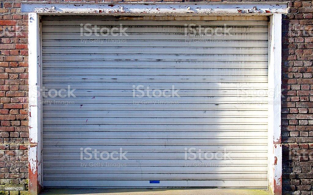 Old dirty rolling steel garage door in brick wall stock photo