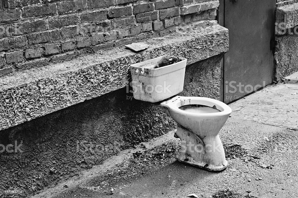 Old dirty toilet in the yard. Black and white royalty-free stock photo
