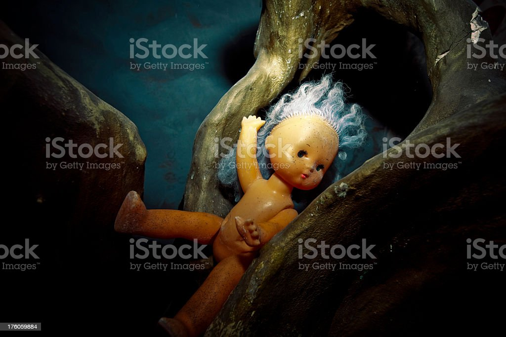 Old doll on surreal tree calling for help royalty-free stock photo