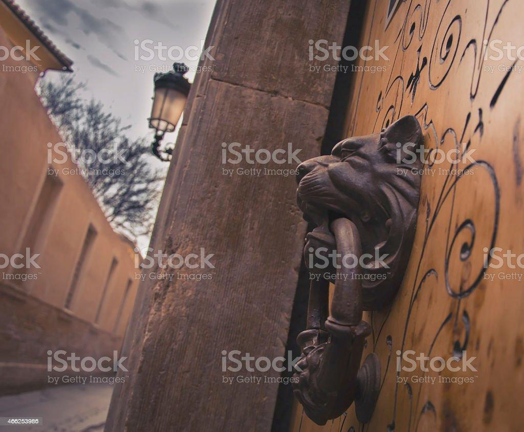 Old door Kocker in a dark street. stock photo