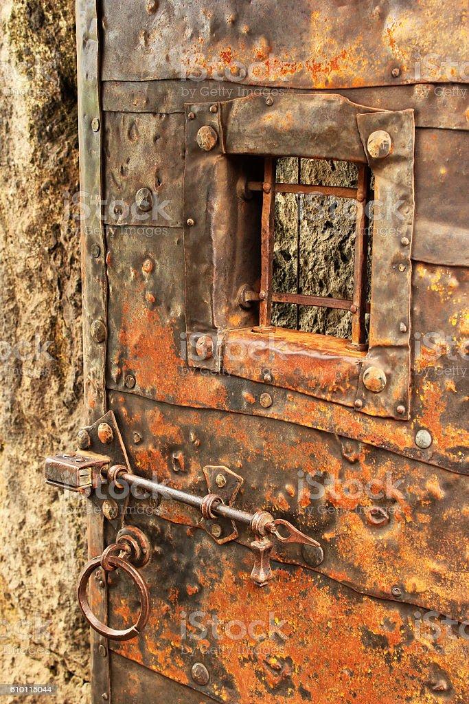 Old door with grilled window, bar lock and ring handle stock photo