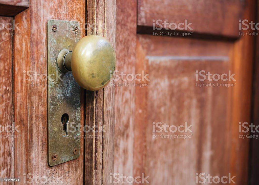 Old Doorknob with keyhole on wooden door stock photo