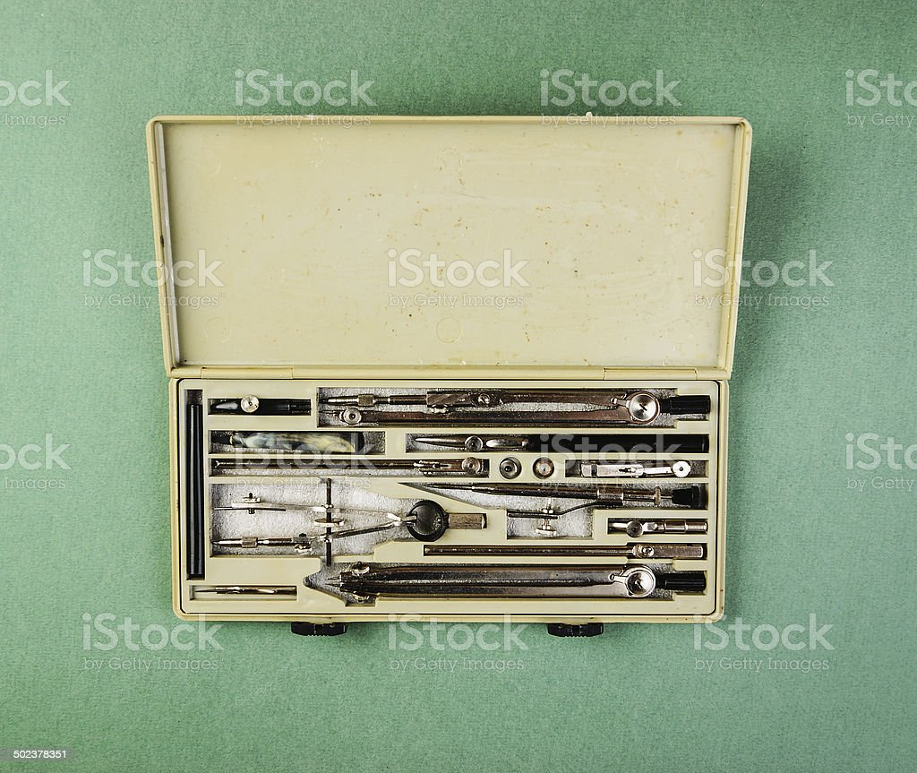 Old drawing tools in a box on a green background royalty-free stock photo