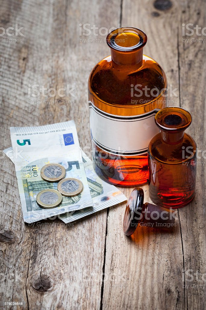 Old drugstore pharmacy bottles Euro coin banknote stock photo