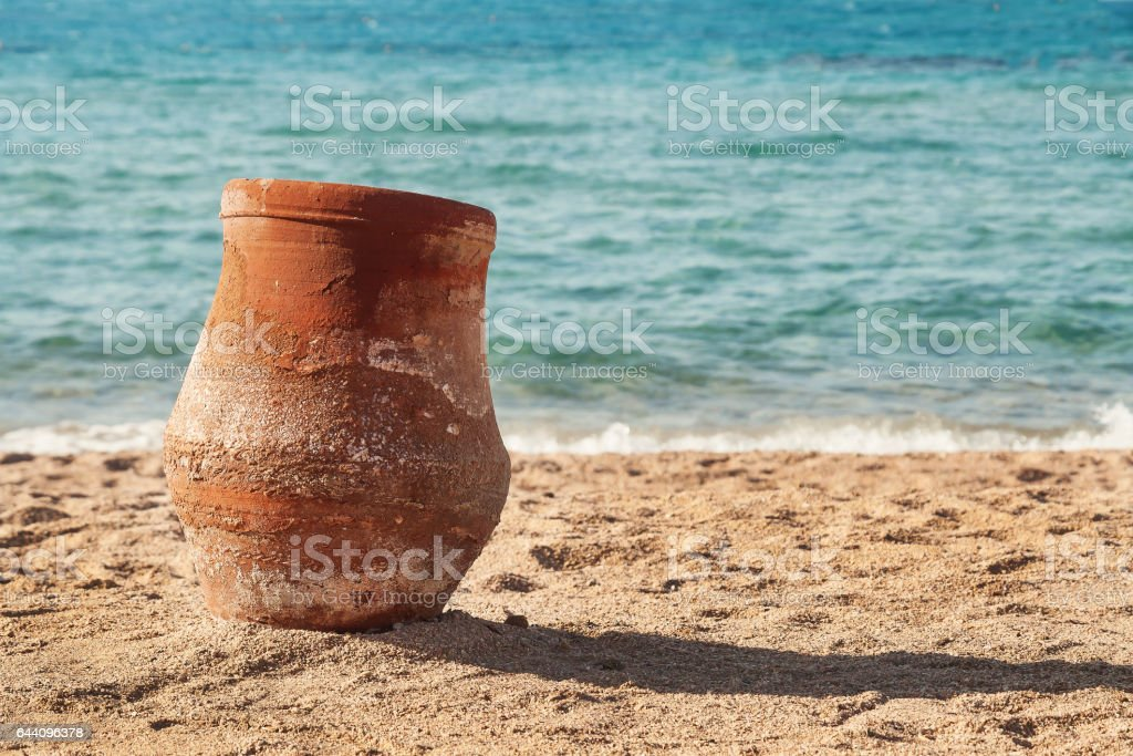 old earthen pitcher standing on the sand near the sea stock photo