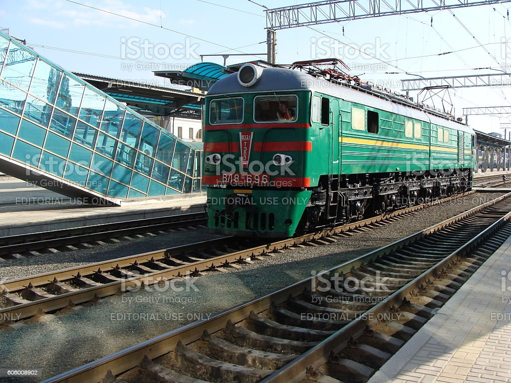 Old Electric Locomotive Arriving at a Modern Railway Station stock photo