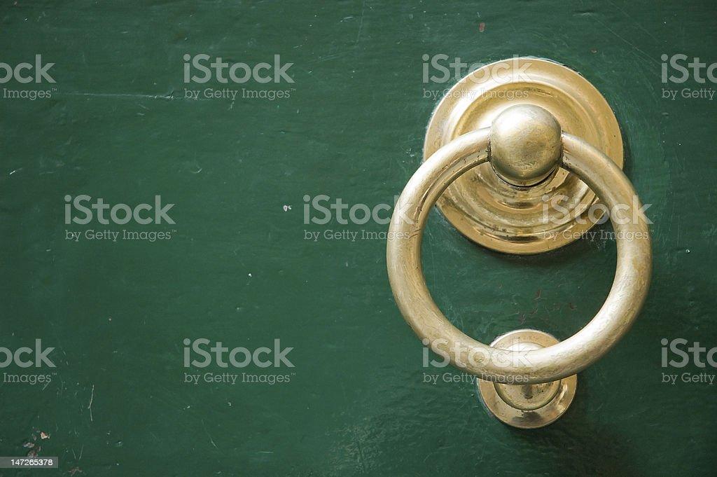 Old elegant golden metal door handle, knocker stock photo