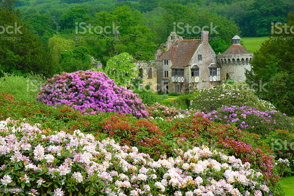 Old English castle surrounded by plenty of trees and flowers stock photo
