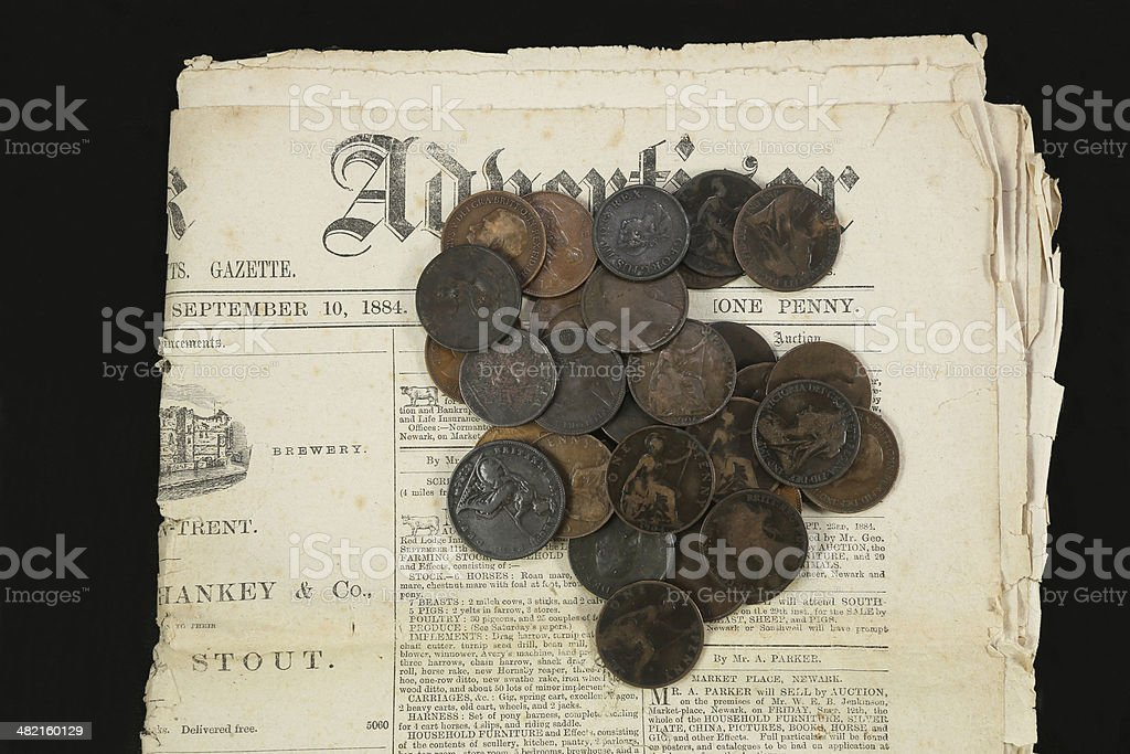 Old English coins piled on a Victorian newspaper stock photo