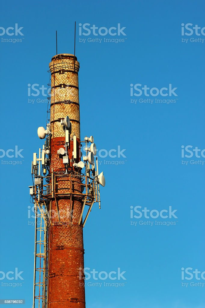 Old factory chimney with antennas stock photo