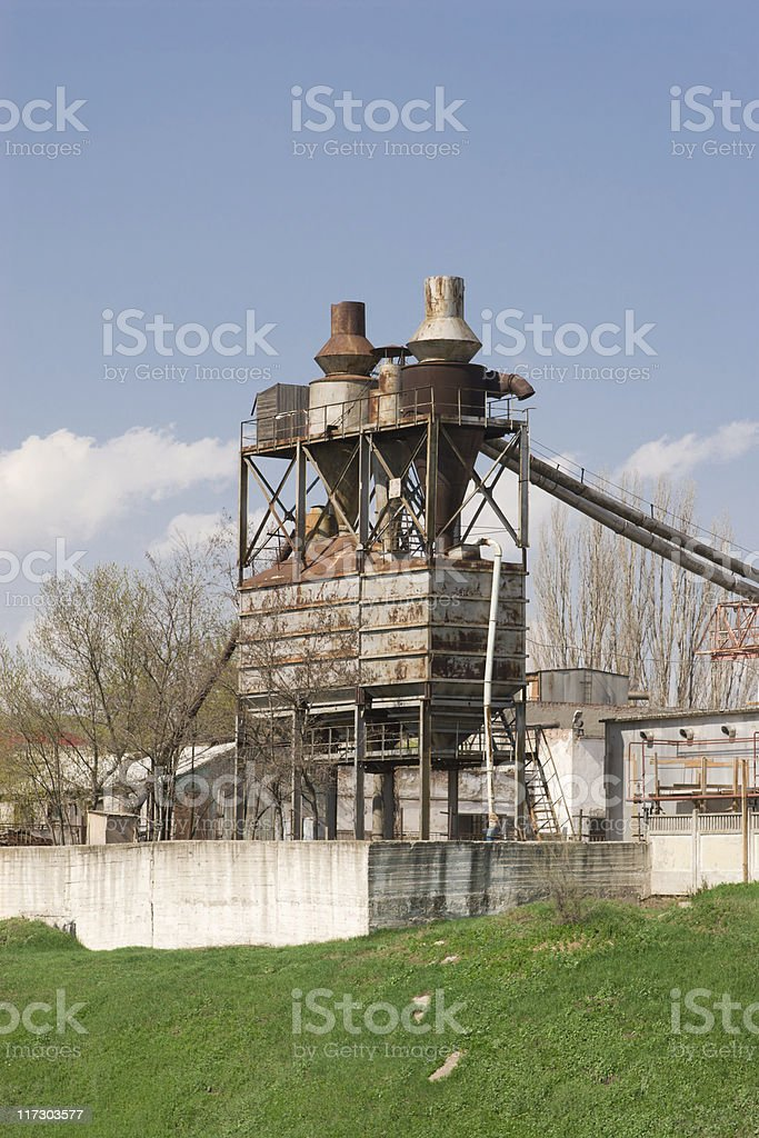 Old factory on a green hill stock photo