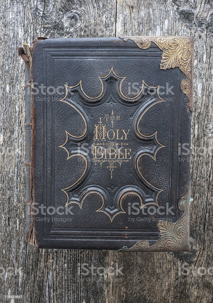 Old family bible with copper edging on wood background stock photo