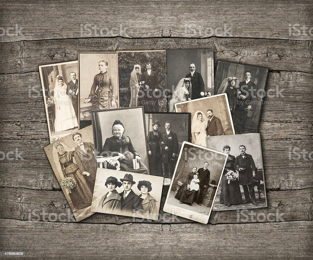 Old family photos laid out on wooden background stock photo