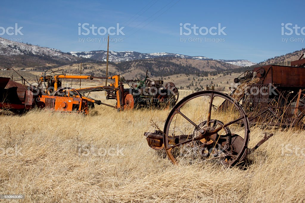 Old farm equpiment in a field stock photo