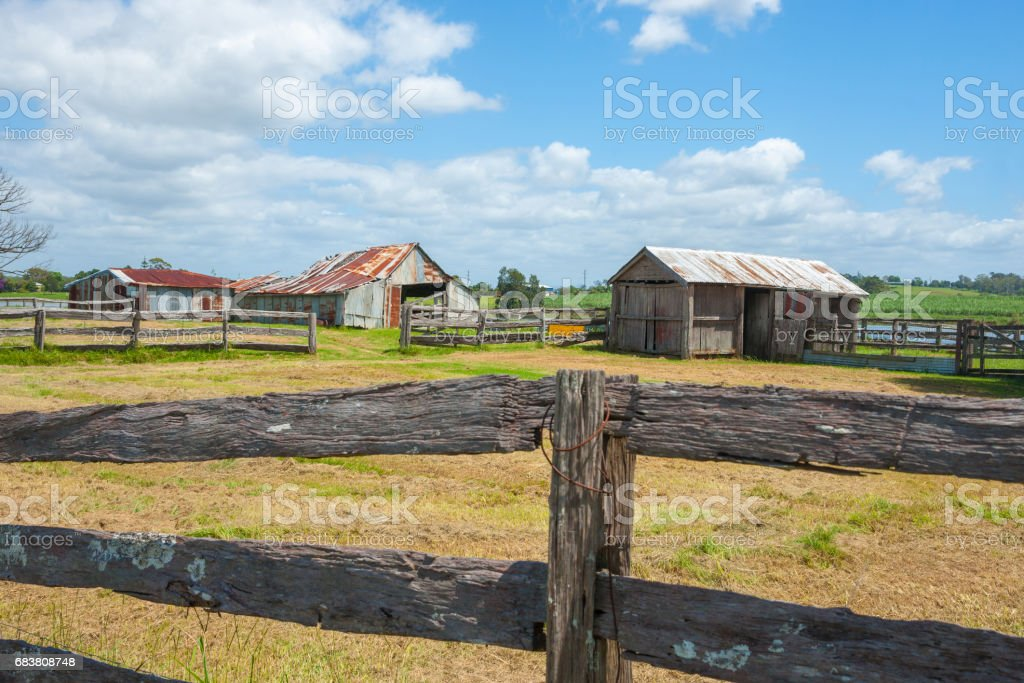 Old farm sheds beyond post and rail fences in rustic rural scene in country Australia  between Ulmarra and Yamba. stock photo