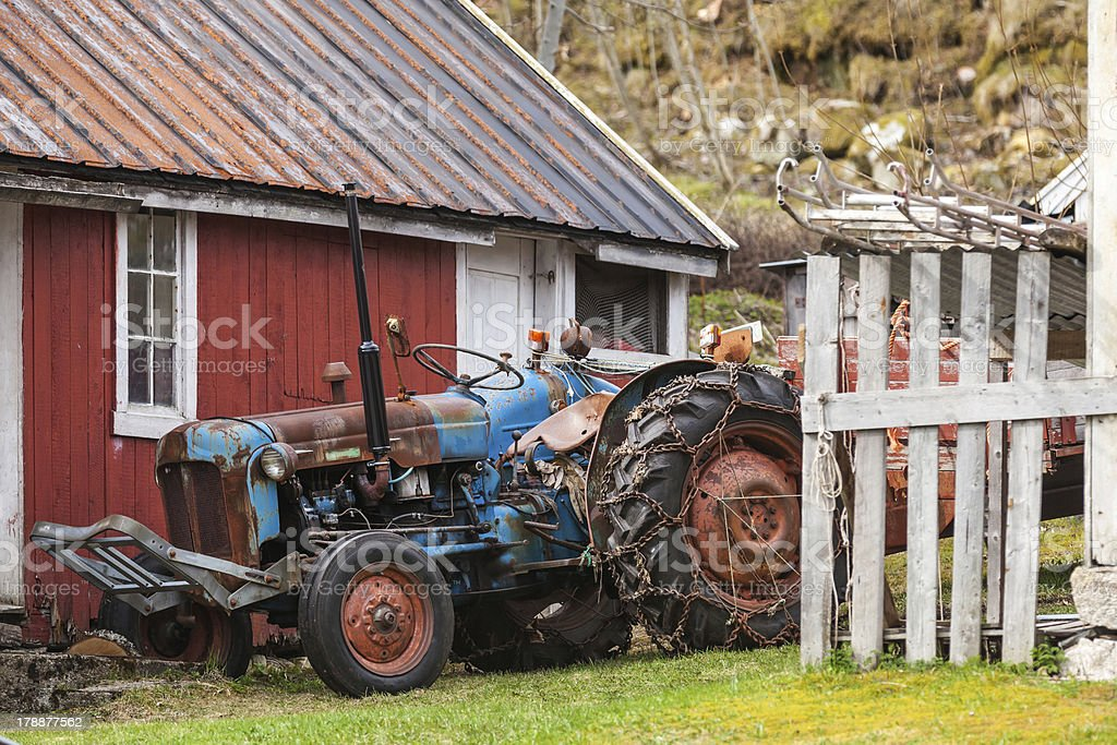 Old farm tractor stands in Norwegian village royalty-free stock photo