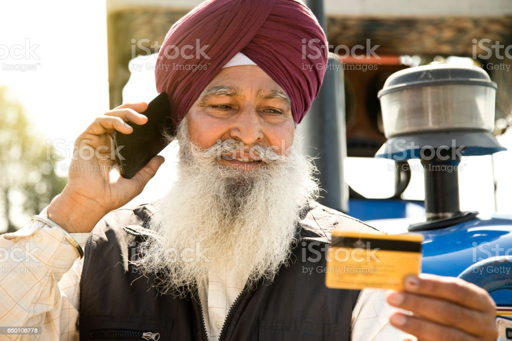Old farmer calling credit card customer support stock photo