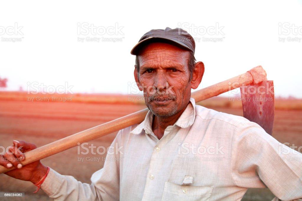 Old farmer holding garden hoe stock photo
