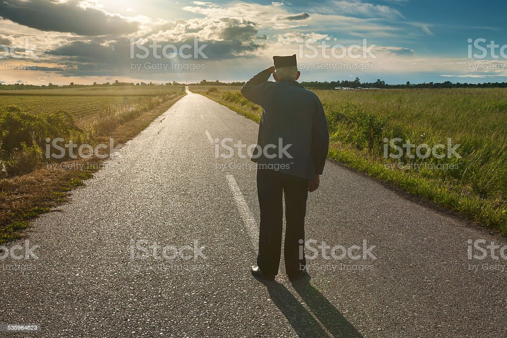 Old farmer standing in middle of the road stock photo