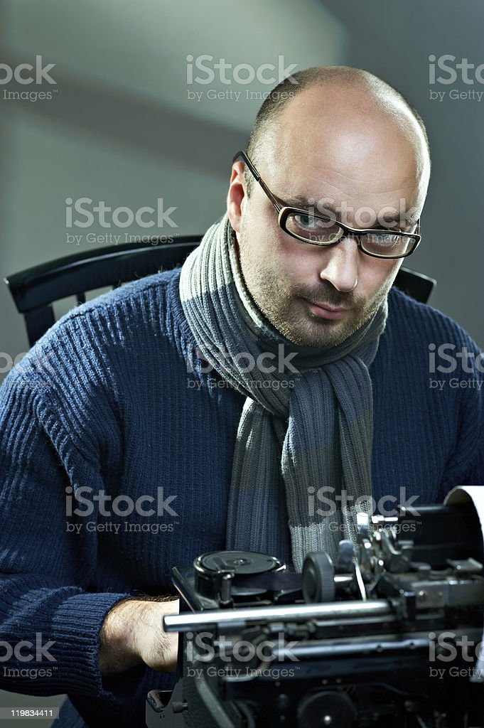 Old fashioned bald writer in glasses writing book stock photo