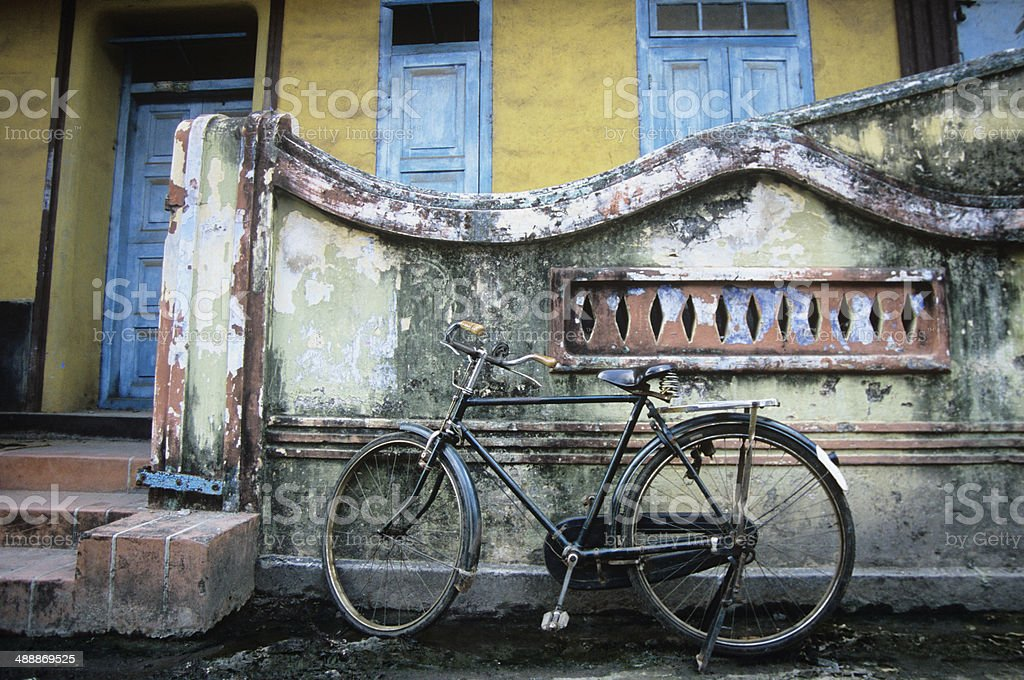 Old fashioned bicycle left by crumbling wall stock photo