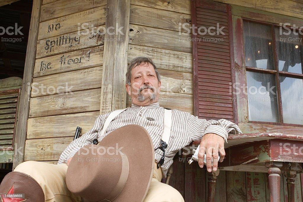 Old Fashioned Caucasian Sheriff Sitting Outside Saloon, Senior Adult stock photo