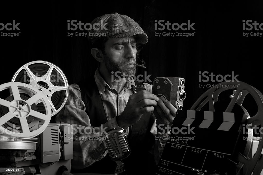 Old Fashioned Cinema Director Posing With Cinema Equipments And Smoking stock photo