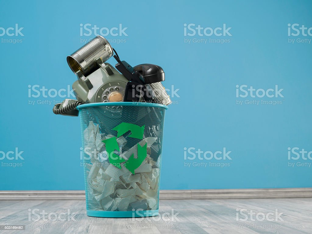 Old Fashioned Communication Tools In Trash Can On Turquoise Wall stock photo