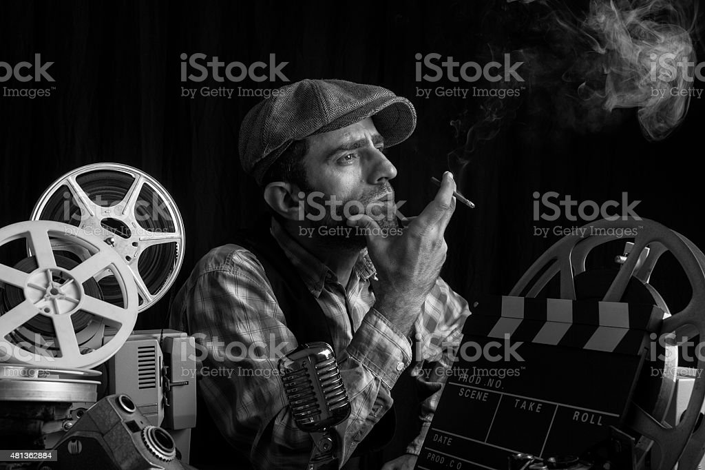 Old Fashioned Film Director Posing With Cinema Equipments And Smoking stock photo