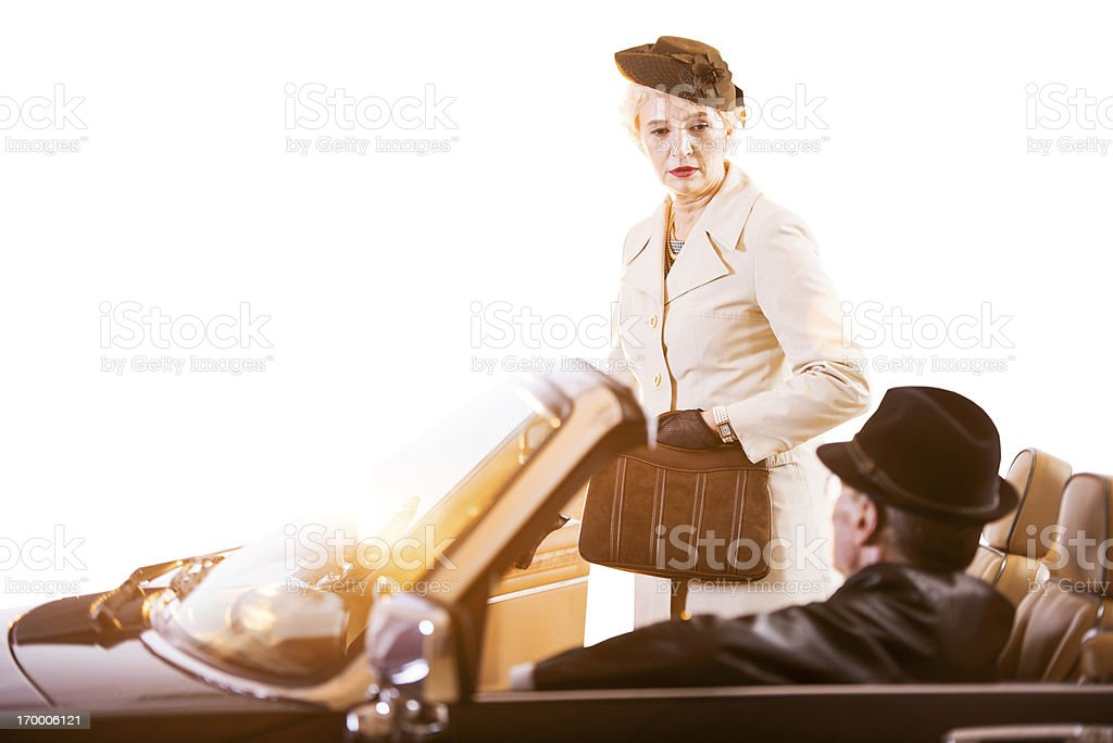 Old fashioned mature lady entering in vintage car. royalty-free stock photo