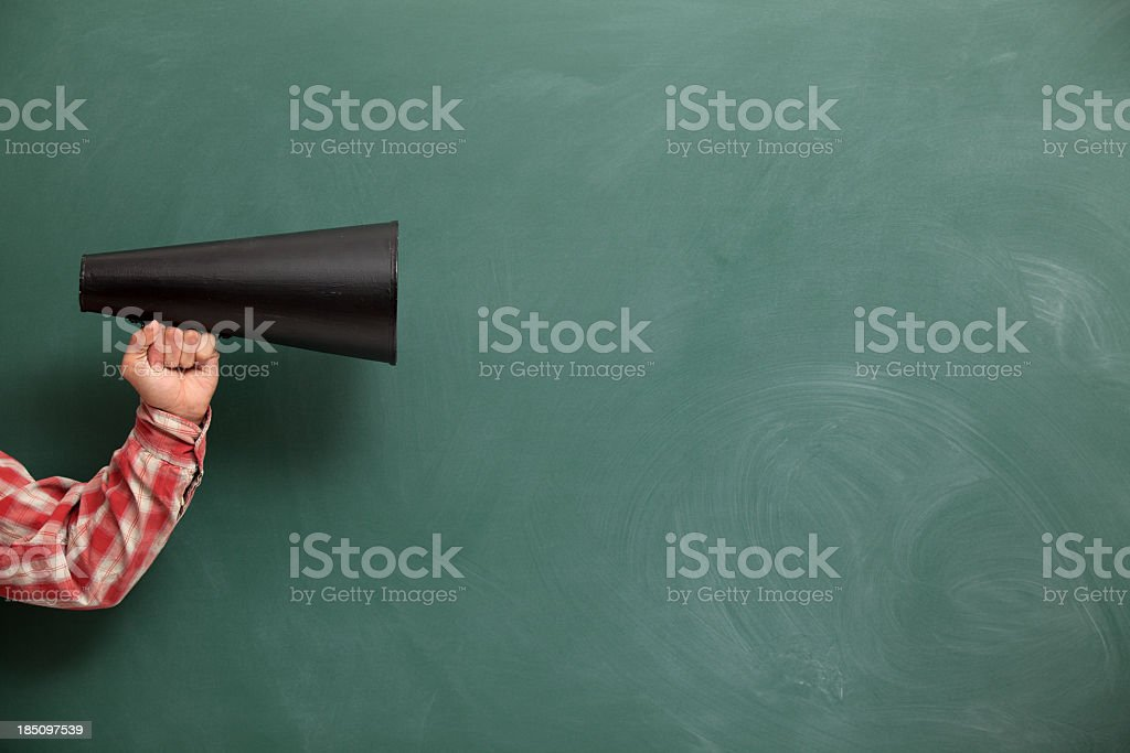 Old Fashioned Megaphone In Human Hand On Green Blank Blackboard stock photo