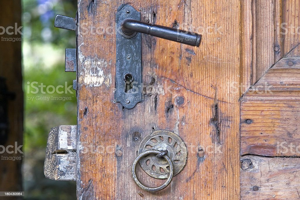 Old fashioned metal knocker on the wooden door royalty-free stock photo