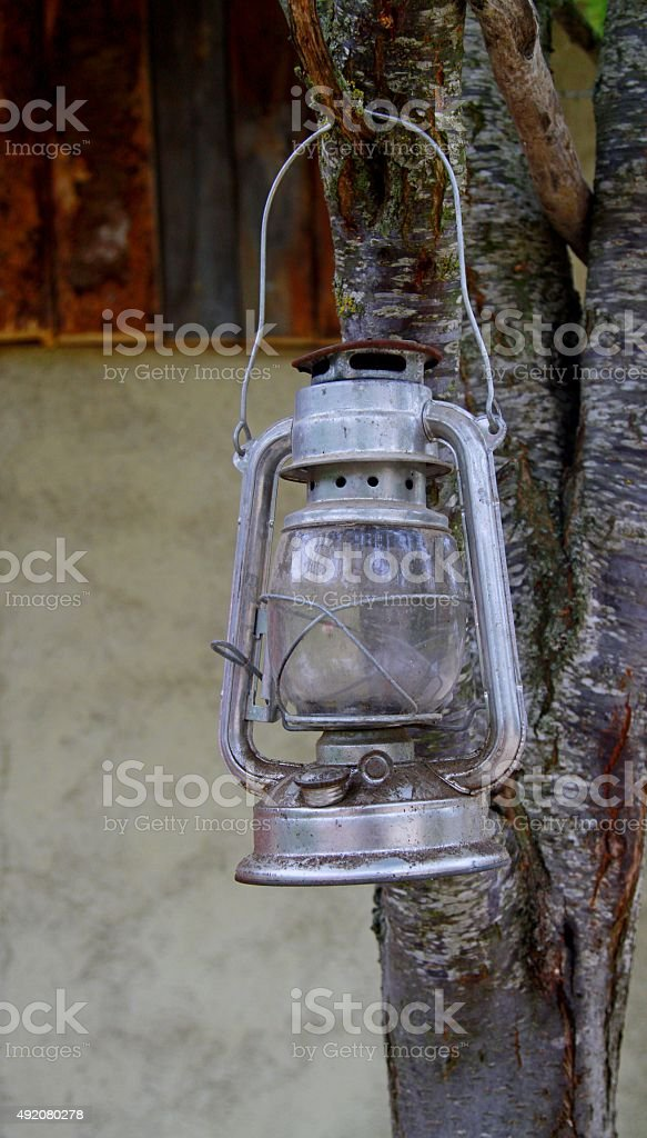 old fashioned oil lamp hanging from tree stock photo