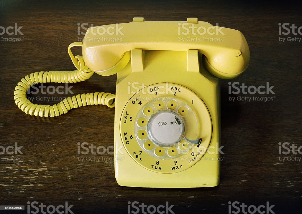 Old Fashioned Retro Yellow Rotary Phone on Wood Table stock photo