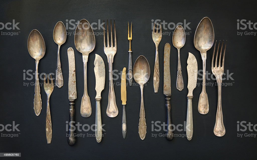 Old fashioned silverware collection on a blackboard, kitchen utensils background stock photo