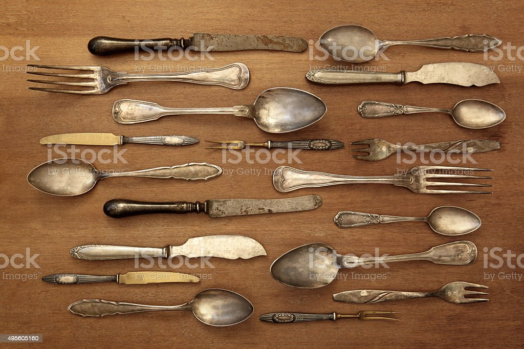Old fashioned silverware collection on a wooden table, kitchen background stock photo