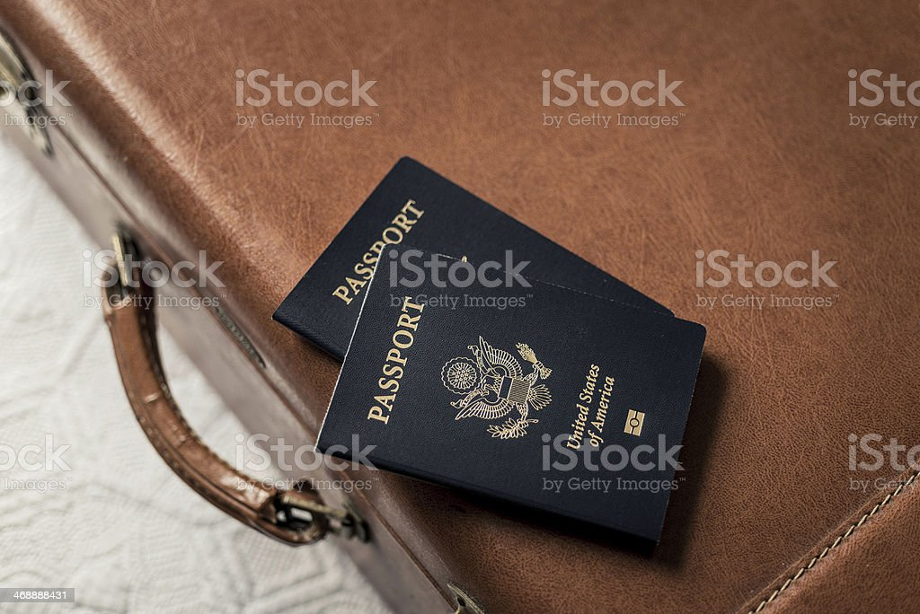 Old Fashioned Suitcase on a Bed with Passports stock photo