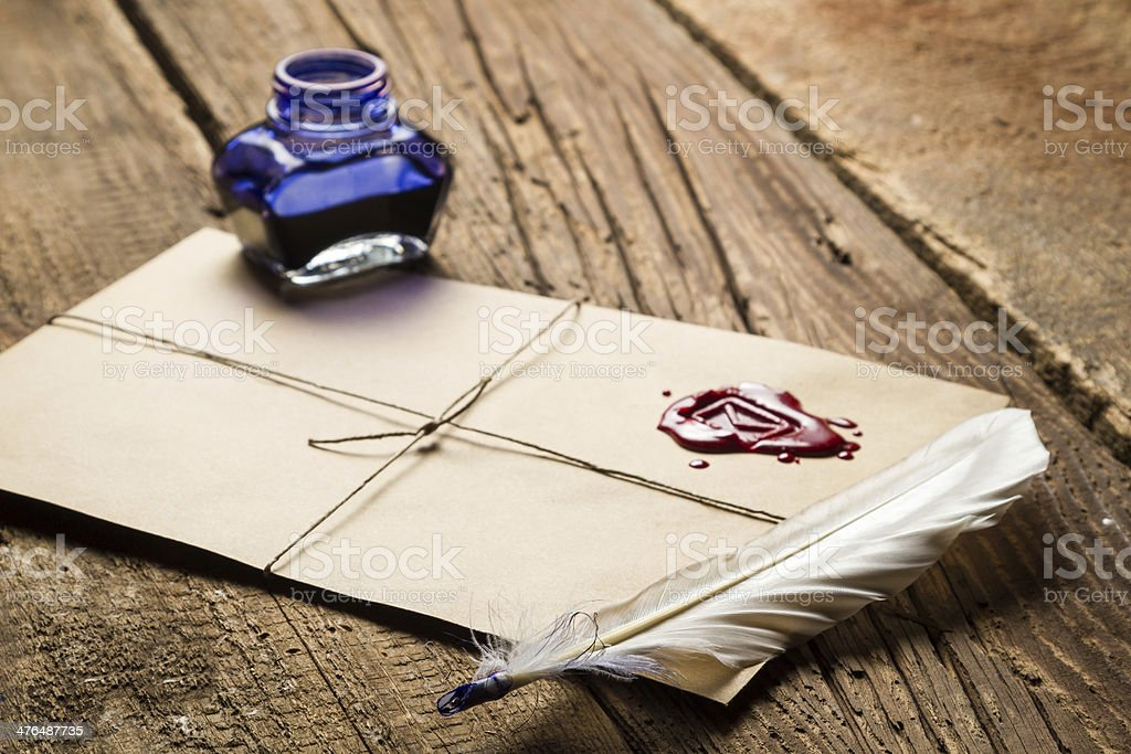 Old feather, envelope, sealing wax and ink bottle royalty-free stock photo