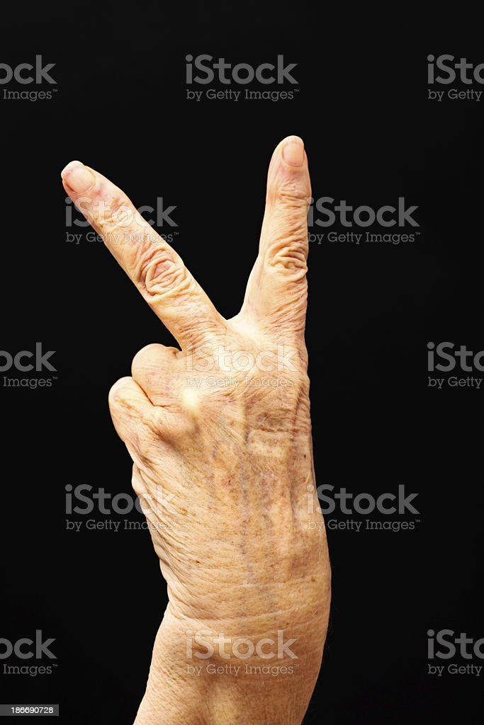 Old female hand makes rude V sign royalty-free stock photo